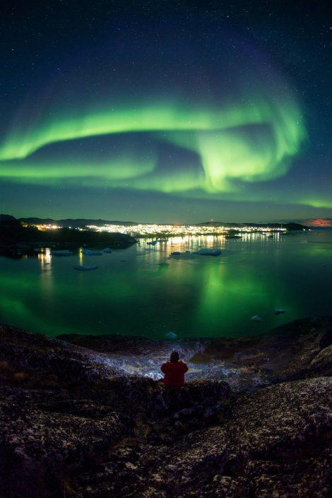 A man with a flash light overlooking Ilulissat, icebergs and northern lights an autumn night. By Paul Zizka