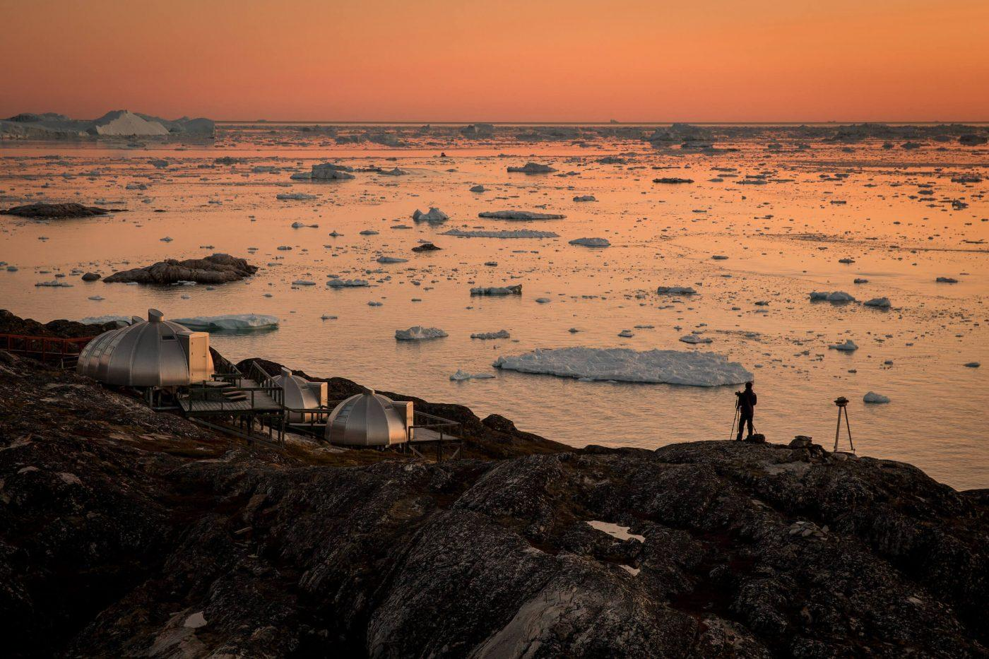 A photographer in the sunset near Hotel Arctic in Ilulissat in Greenland. By Mads Pihl