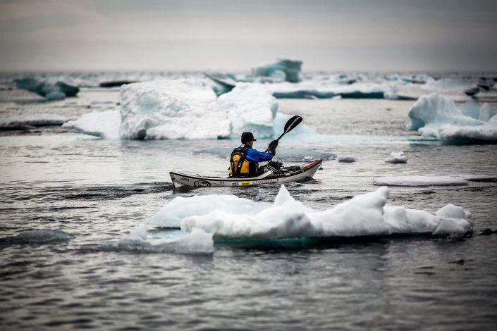 A sea kayaker among ice floes near Tasiilaq in East Greenland