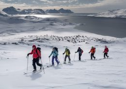 A group of skiers climbing a mountain near Kulusuk on a ski touring trip in East Greenland. Photo by Mads Pihl - Visit Greenland