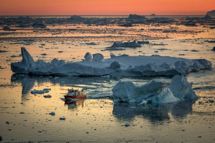 A small passenger boat in the sunset near Ilulissat in Greenland. By Mads Pihl