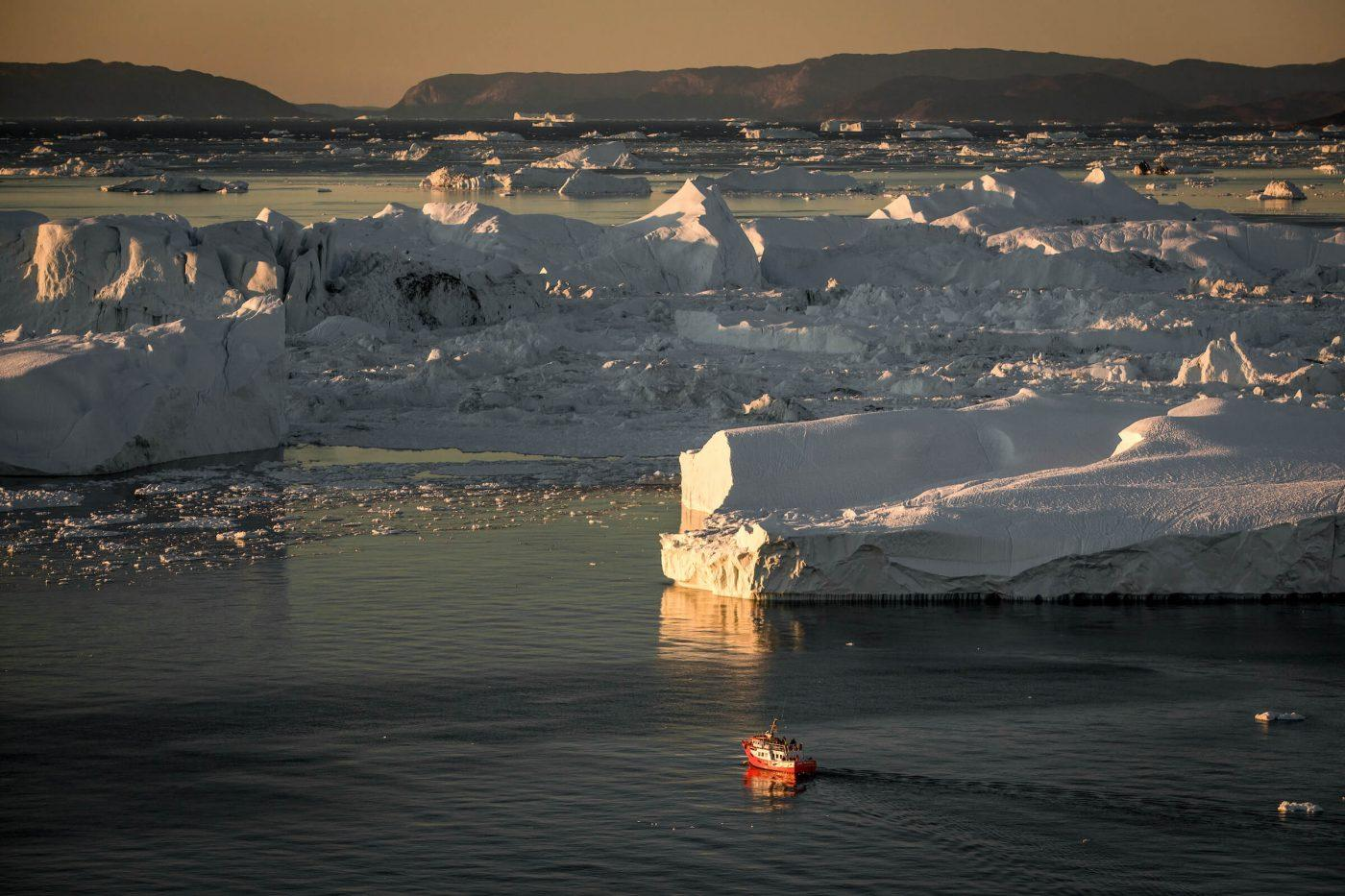 A small passenger boat near the big icebergs at Ilulissat ice fjord in Greenland. Photo by Mads Pihl