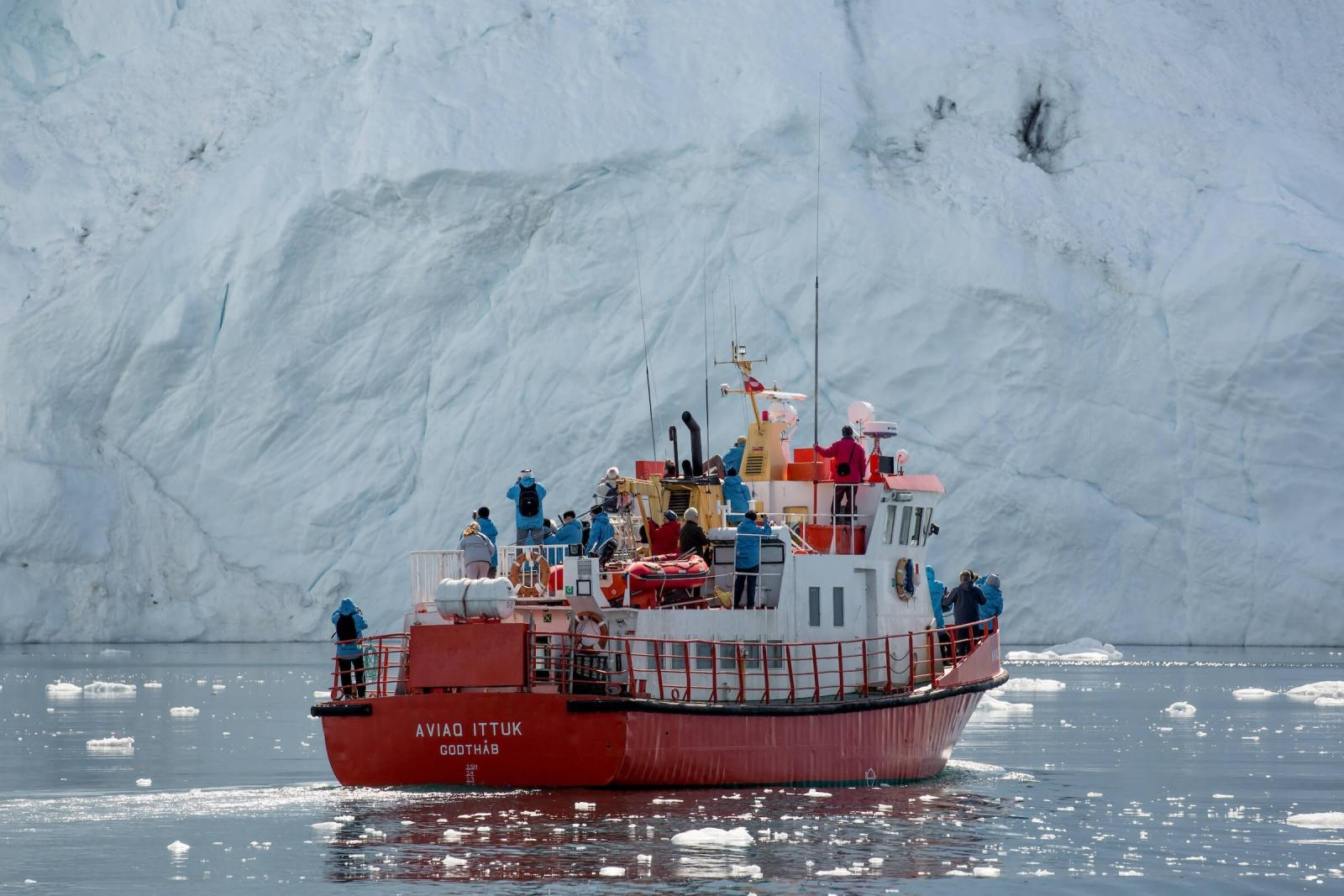 A tour boat in front of an iceberg wall near Ilulissat in Greenland. Photo by Mads Pihl