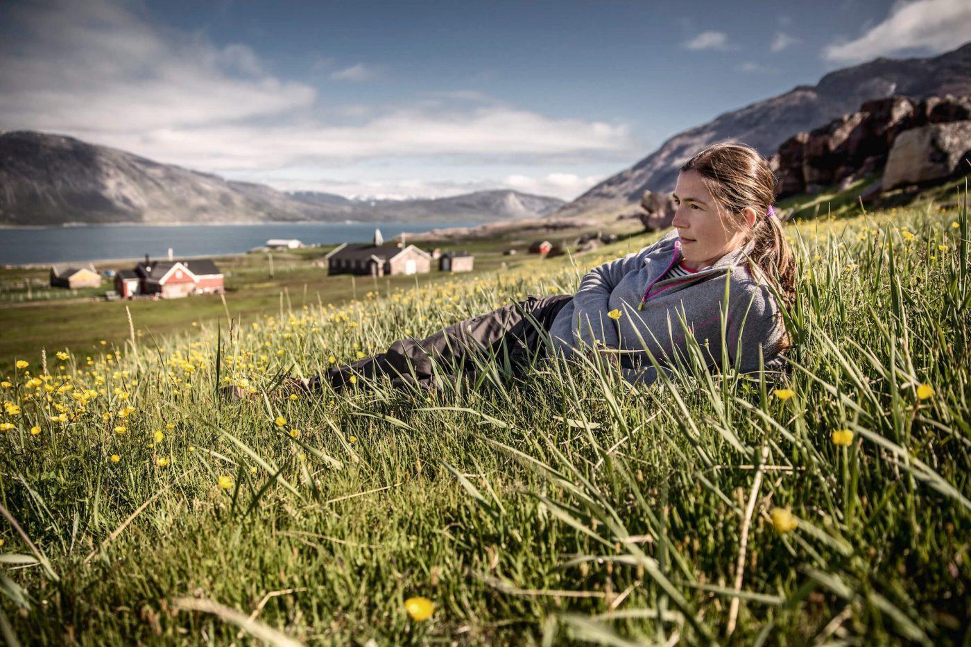 A traveler enjoying the summer sun in Igaliku in South Greenland. By Mads Pihl