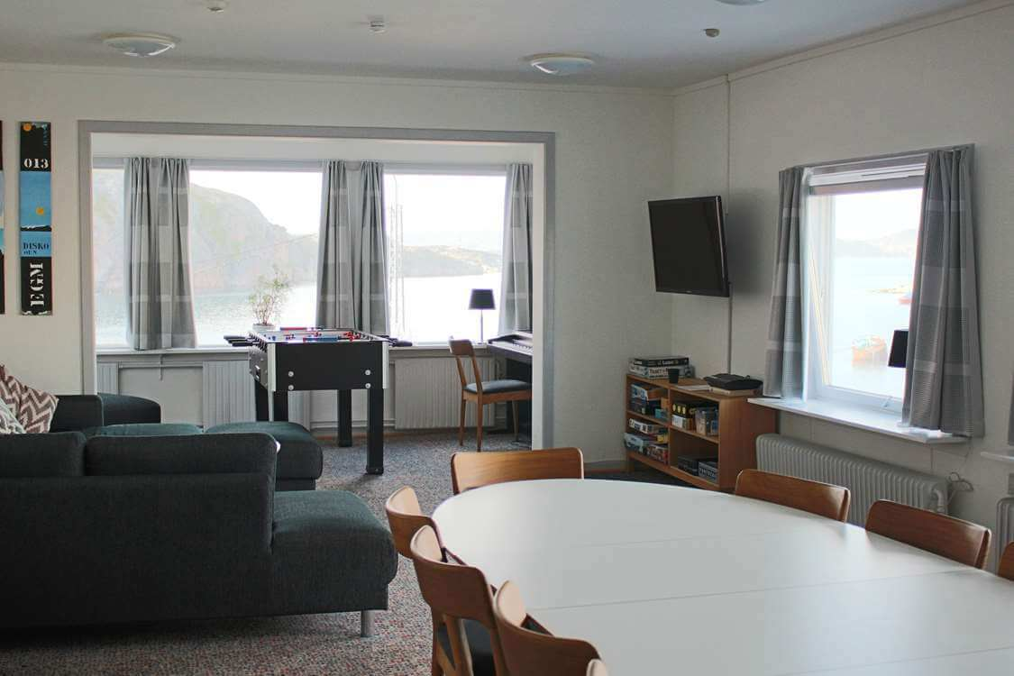 Bright living area with dining table, TV, table soccer and comfortable couch. Photo by Aasiaat Sømandshjem, Visit Greenland