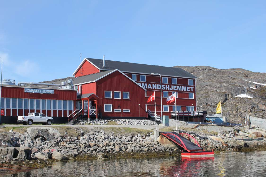 The Aasiaat Seamen's Home from outside on a sunny day. Photo by Aasiaat Sømandshjem, Visit Greenland