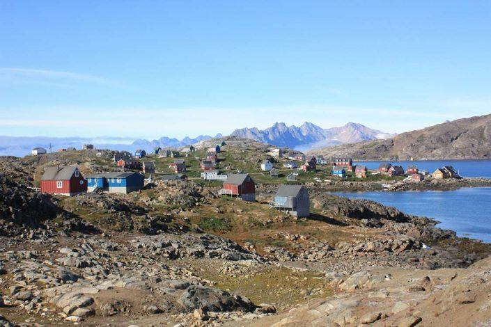 View of greenlandic city by the coast with mountains in the background