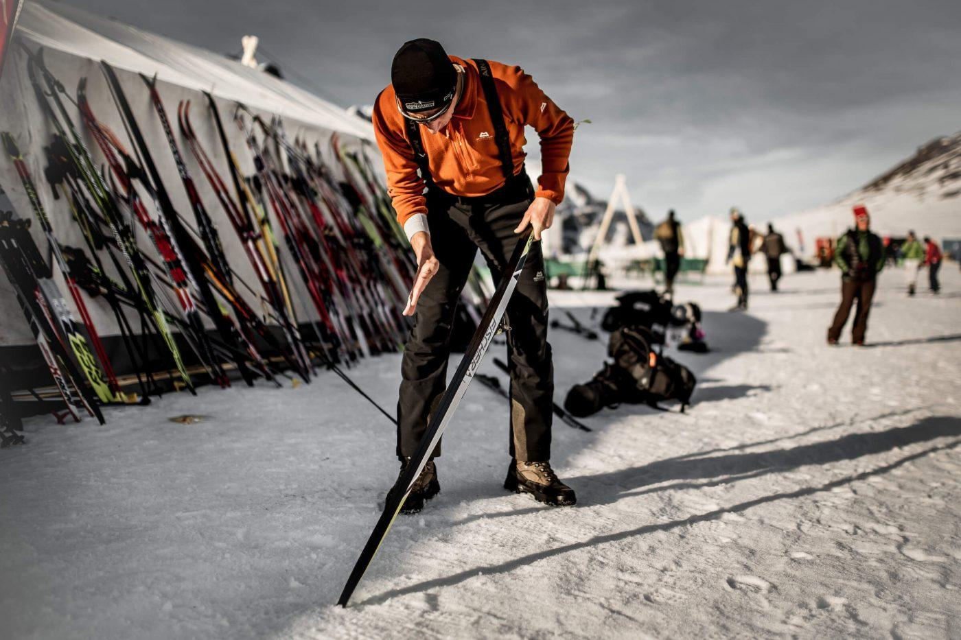 A skier in the Arctic Circle Race camp preparing his skis. Photo by Mas Pihl, Visit Greenland
