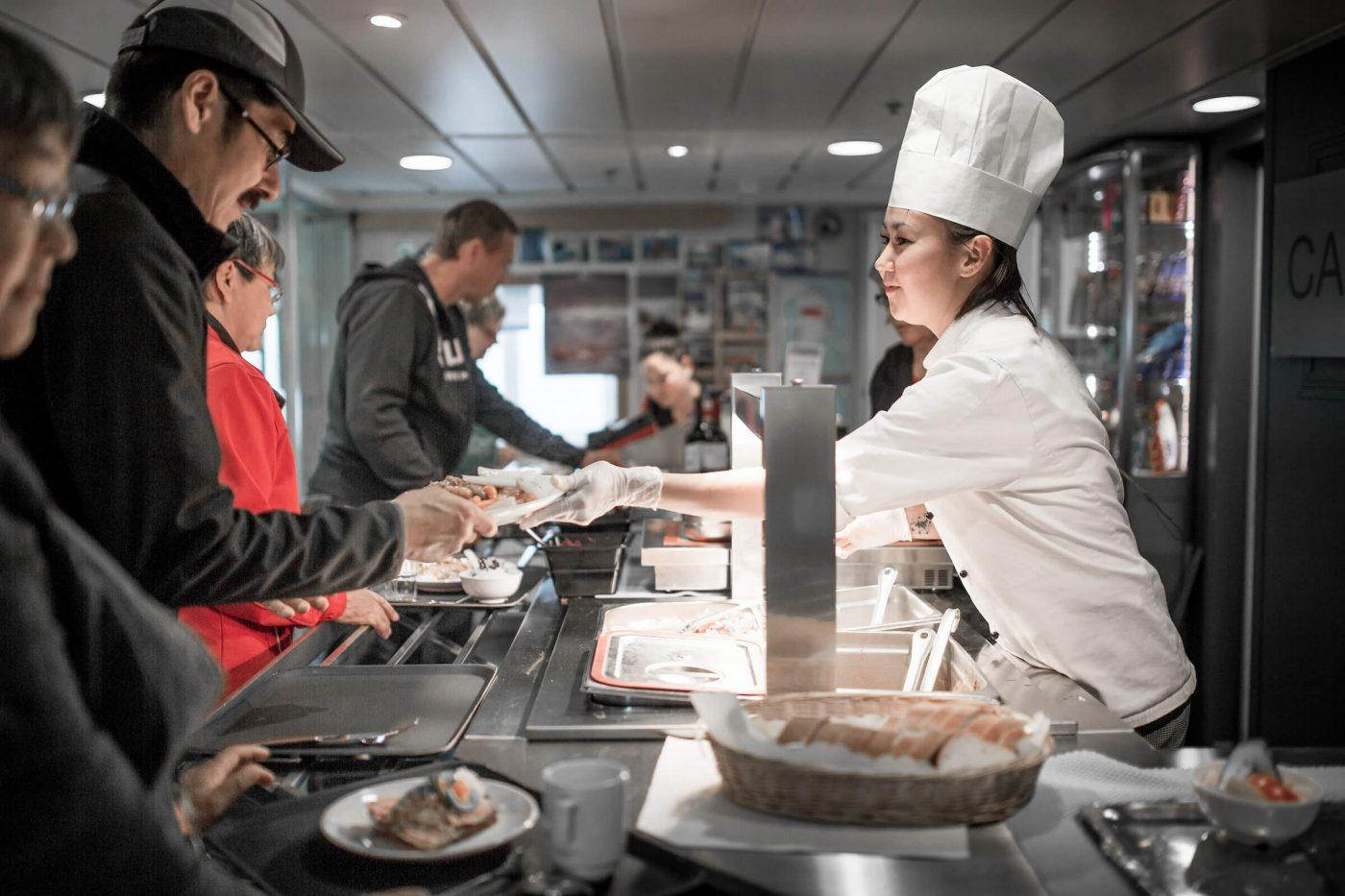 A chef serving dinner on board the passenger ferry Sarfaq Ittuk in GreenlandGuests in one of the cabins in Sarfaq Ittuk. Visit Greenland