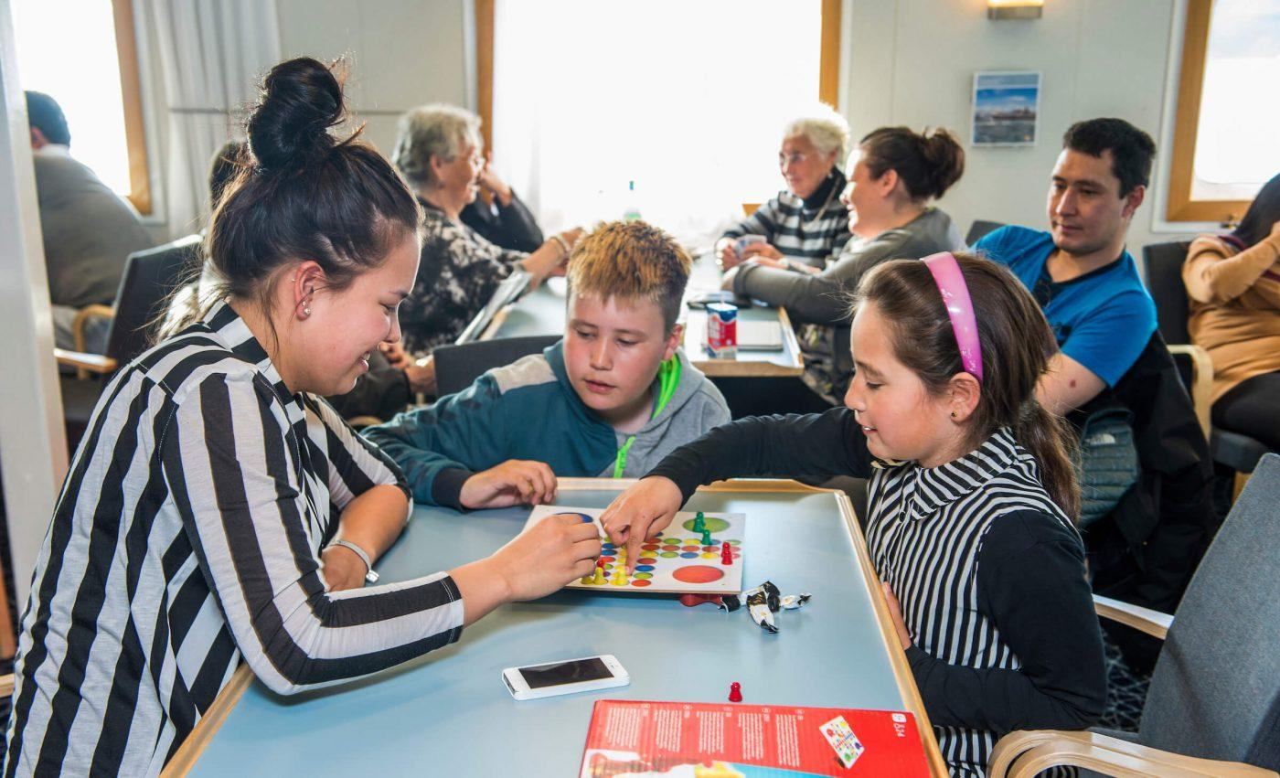 A young woman playing ludo with kids in Cafe Sarfaq in the coastal ferry called Sarfaq Ittuk in GreenlandGuests in one of the cabins in Sarfaq Ittuk. Visit Greenland
