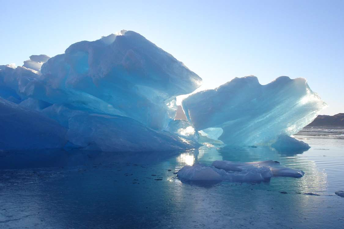Two icebergs in sunlight. Photo by Blue Ice Explorer