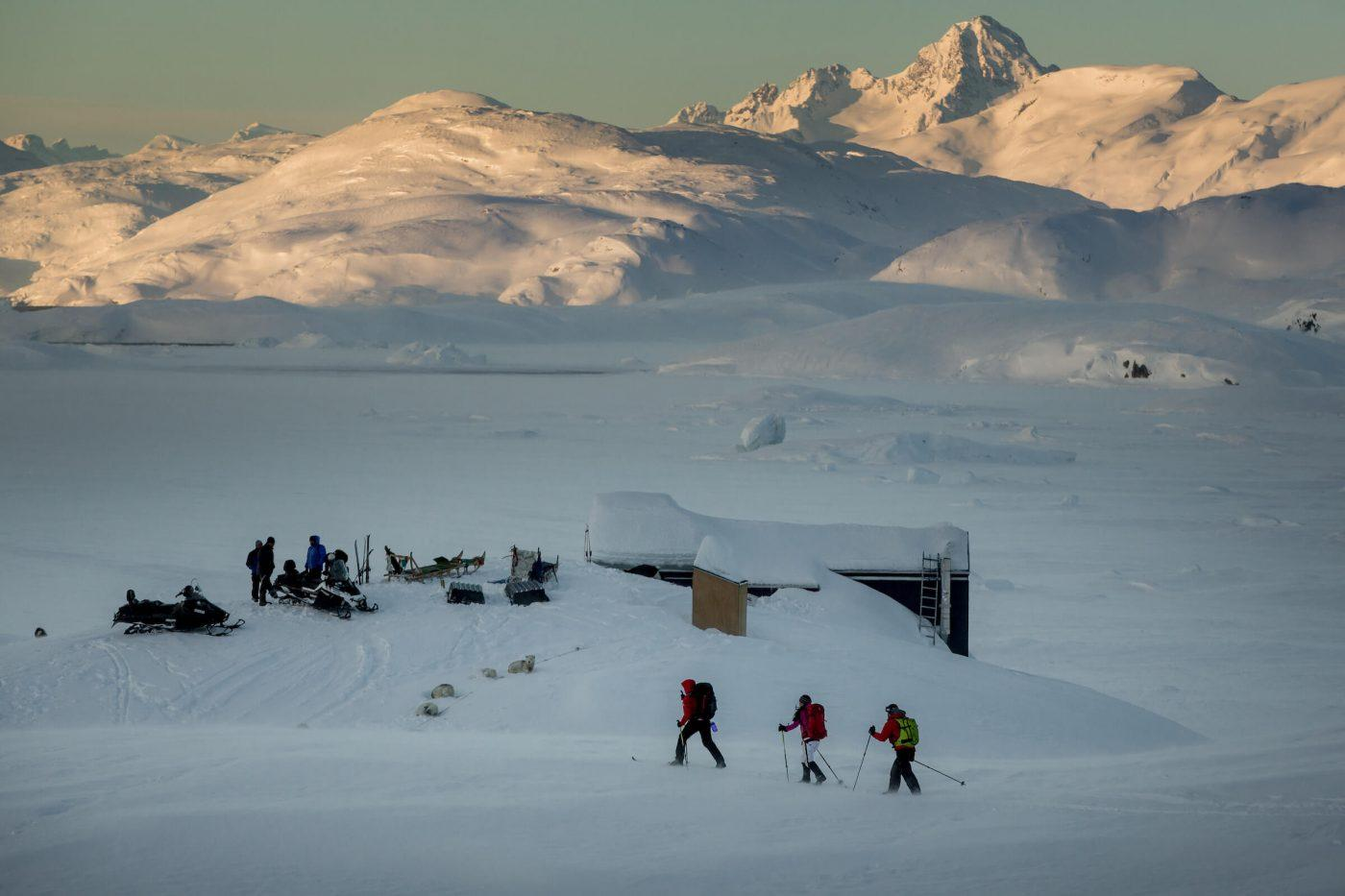 Cross country skiers approaching the Travellodge Greenland hut at Sermilik ice fjord in East Greenland. By Mads Pihl