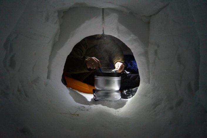 Guide heating food in iglo over a camping stove. Photo by Diskobay Adventures, Visit Greenland