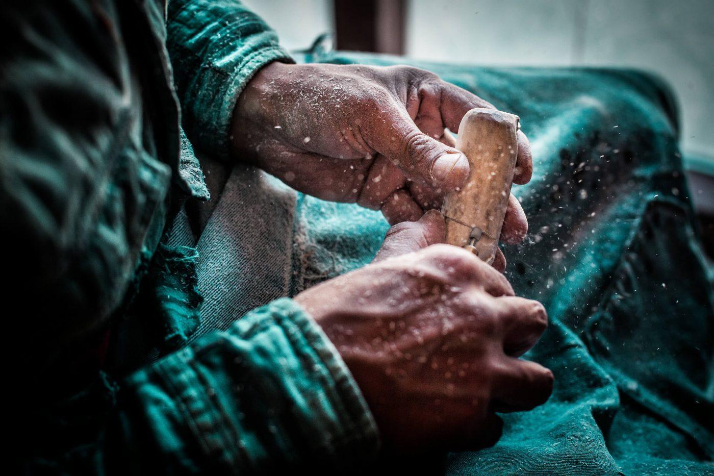 Enok Kilime carving reindeer bone in Sisimiut in Greenland - by Mads Pihl