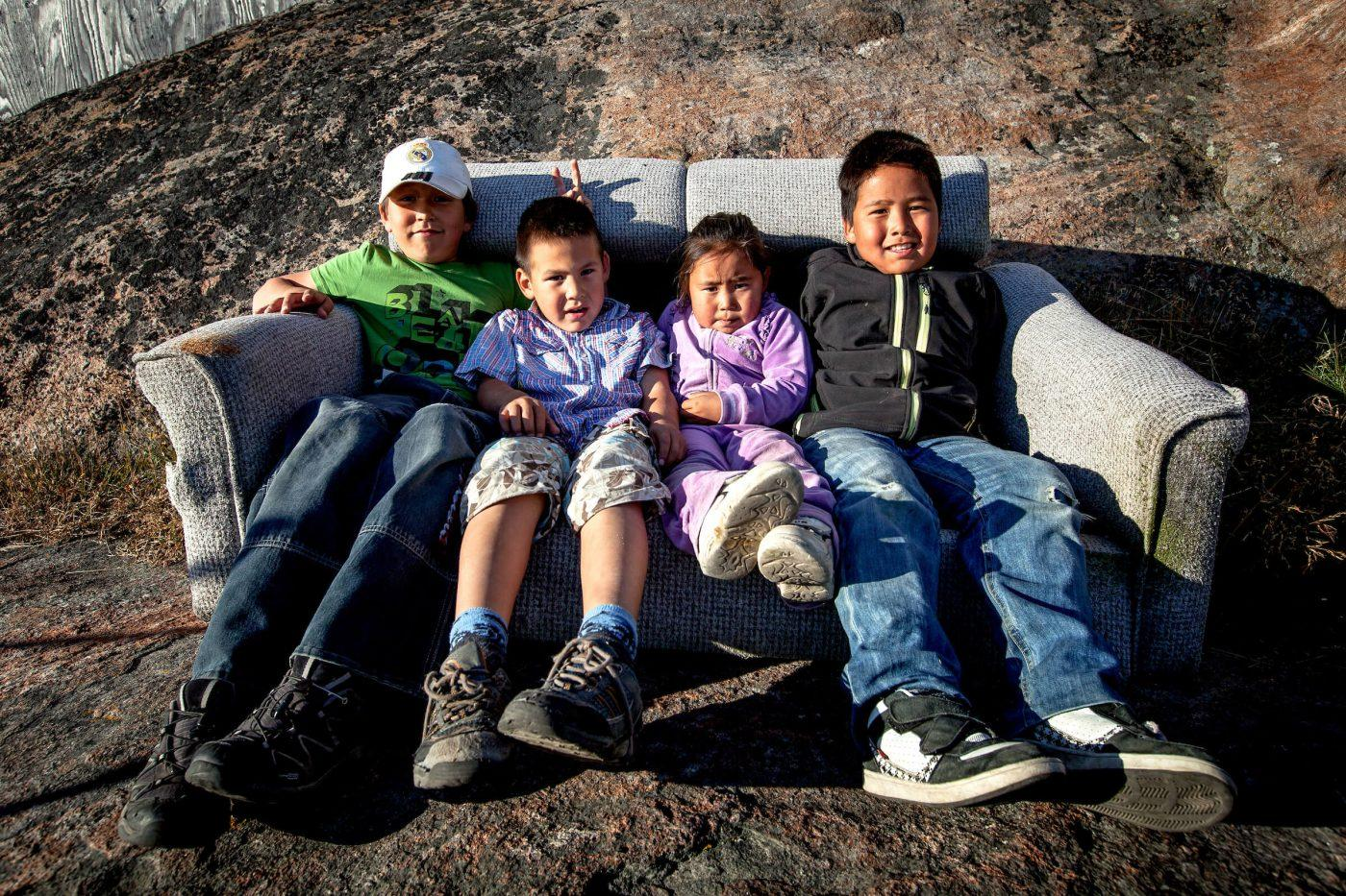 Four kids from Kangaamiut in Greenland hanging out in an outdoor sofa. Photo by Mads Pihl