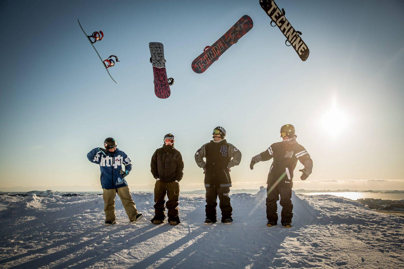 Four snowboarders from Nuuk in Greenland thowing their snowboards in the air. Photo by Mads Pihl