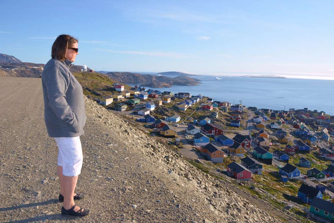 Woman looking over the sea and Upernavik. Photo by John Kislov