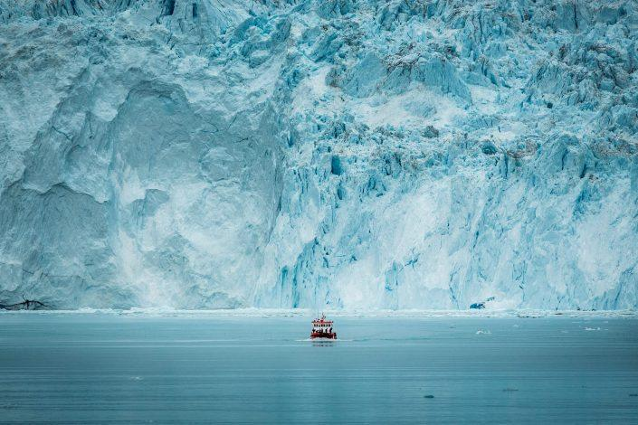 A small passenger boat in front of the huge glacier wall at the Eqi glacier in Greenland