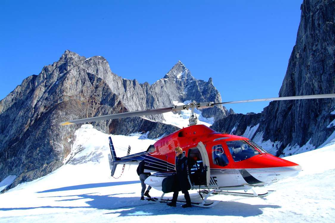 A helicopter in between large mountains. Photo by Arctic Dream, Visit Greenland