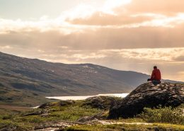 Hiker enjoys a relaxing and reflective moment in the Arctic Circle backcountry. By Raven Eye Photography