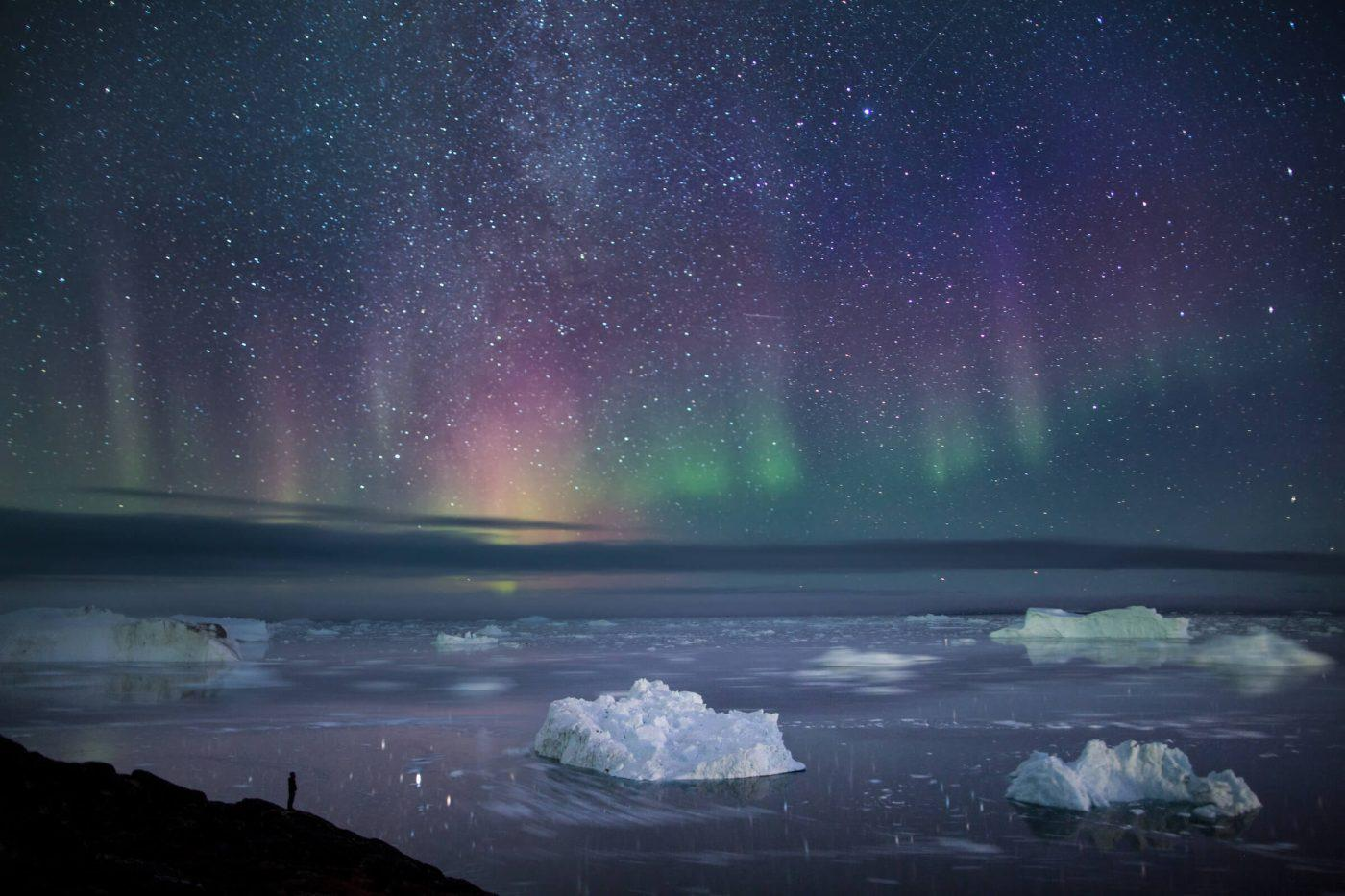 Hiker in Ilulissat, North Greenland standing at the Sermermiut overlook close to the Ilulissat Icefjord gazing at icebergs and a crisp autumn night sky filled with stars and northern lights. By Paul Zizka