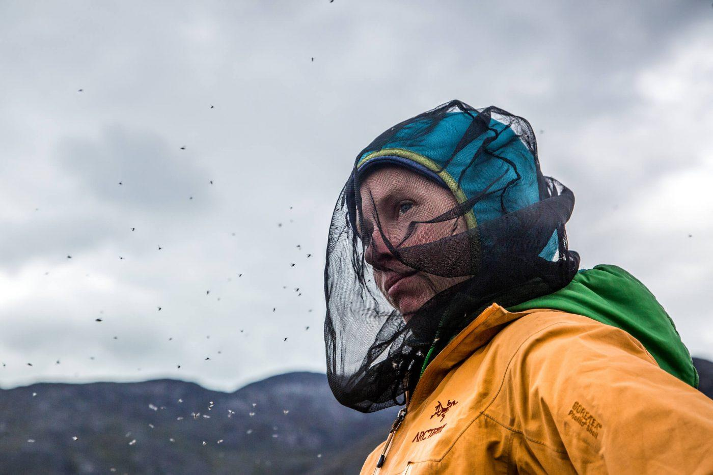 Hiker wards off pesky mosquitos by wearing a mosquito head net while adventuring in Nuuk Fjord. Photo by Raven Eye Photography