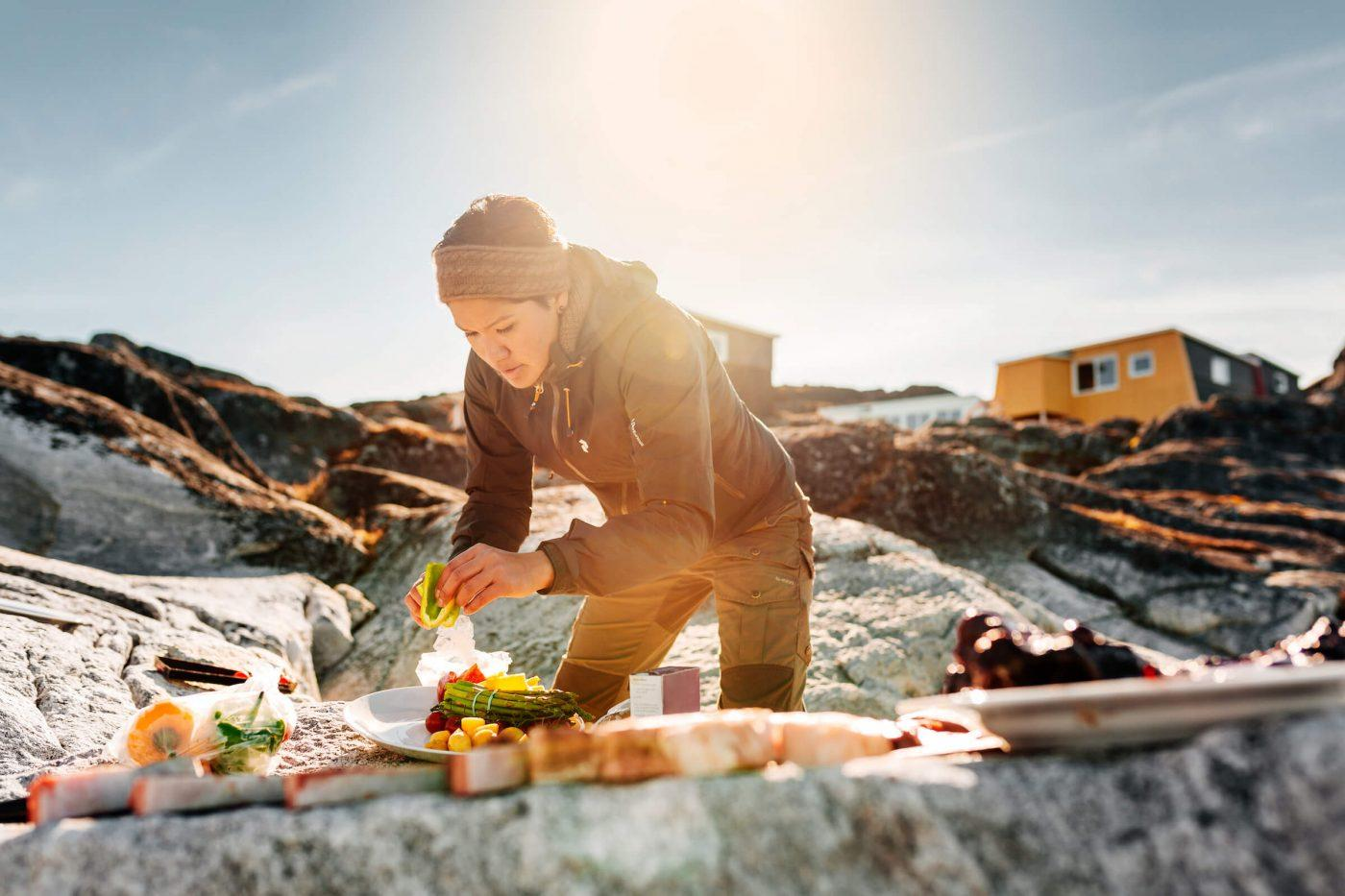 Woman preparing Greenlandic specialties on the rocks on the beach by Inuk Hostels in Nuuk in Greenland. Photo by Rebecca Gustafsson – Visit Greenland