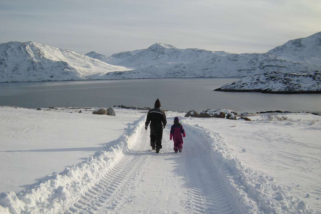 Father and daughter on a walk in South Greenland with snow covered mountains in the horizon. Photo by Agathe Devisme