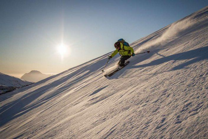 Alpine skier skiing offroad in sunny weather. Photo by Kangerluarsunnguaq Ski Center