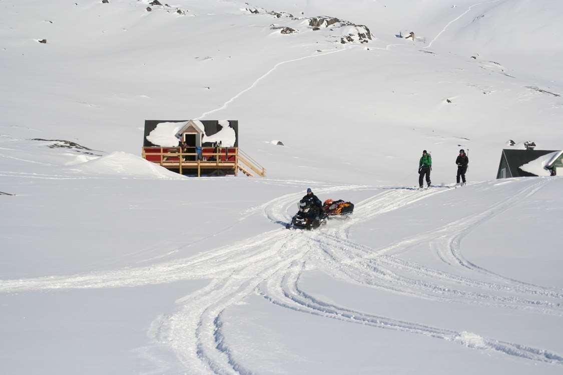 Snowmobile dragging skiers across the snow. Photo by Kangerluarsunnguaq Ski Center
