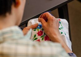 Woman sewing flower patterns onto kamik - a part of the Greenlandic national costume. Photo by Kittat Economusee