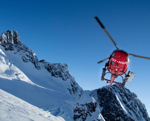 Air Greenland helicopter flying above mountains. By Humbert Entress