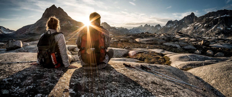 Midnight Sun - Two hikers enjoying the sunset near Qenertivartivit in Ammassalik Fjord near Kulusuk in East Greenland
