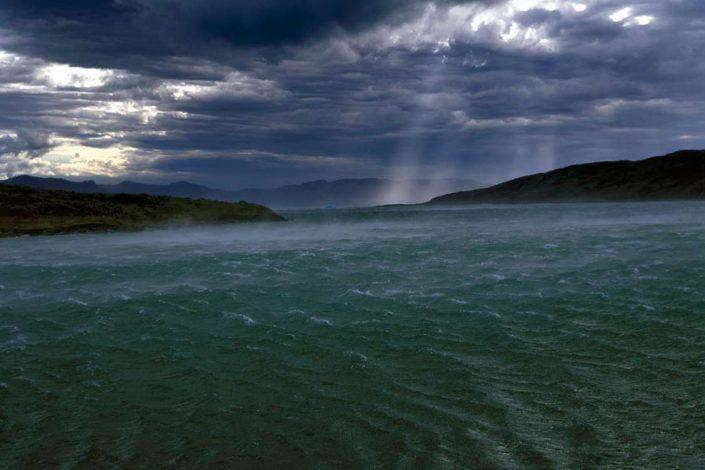 Windy and rainy weather shows waves in the ocean while sunlight peeks through the skies in Tasermiut Fjord of South Greenland. Photo by Nanortalik Tourism Service