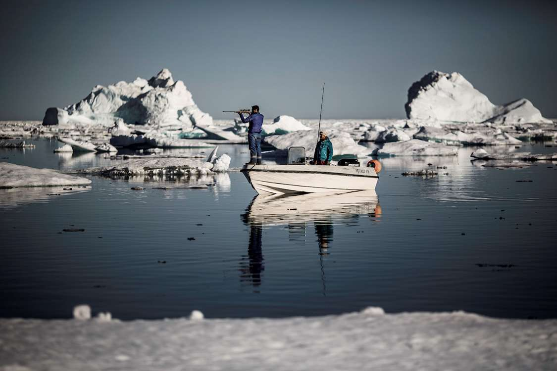 Two hunters in the sea ice near Tasiilaq in East Greenland. Photo by Mads Pihl - Visit Greenland