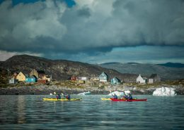 PGI Greenland kayakers paddling past Oqaatsut in the Disko Bay in Greenland. Photo by Mads Pihl - Visit Greenland