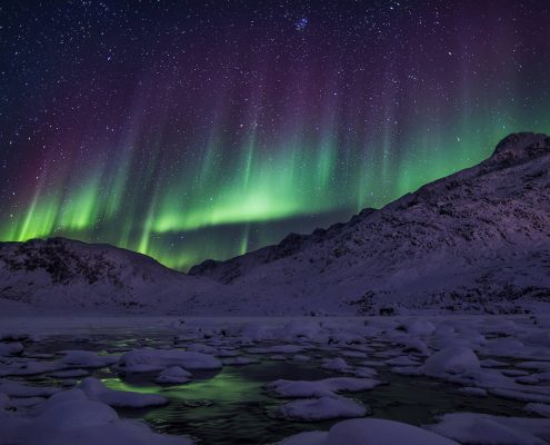 Northern lights over mountains. By Mads Pihl