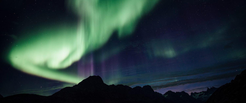 Northern lights over a lit tent, Camp In Tasiilaq Fjord. By Chris Brinlee Jr