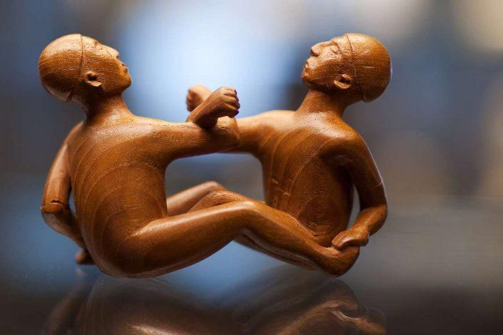 Wooden sculpture of two Inuit men playing the arm pull Inuit game. Photo by Rebecca Gustafsson