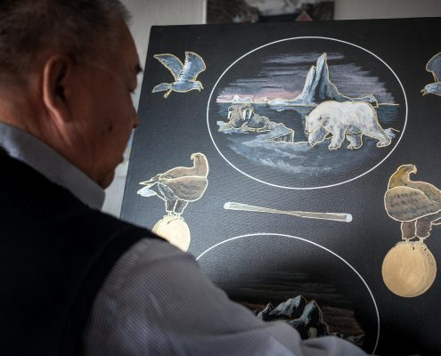 Painter Kristian Lennert from Sismiut at work in his home in Greenland - by Mads Pihl