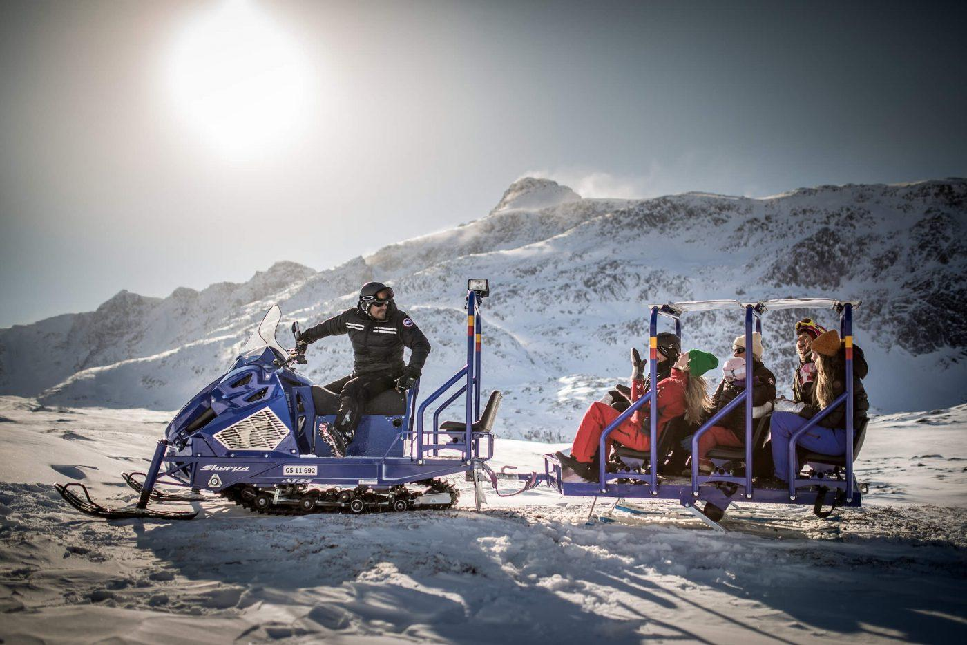 Passengers on the Sisimiut snowmobile bus in Greenland having fun in the sun. Photo by Mads Pihl