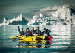 Kayakers mong icebergs near Ilulissat and Oqaatsut in North Greenland