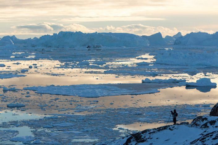 Photographer shooting the Ilulissat icefjord in North Greenland on a cloudy day. By Paul Zizka