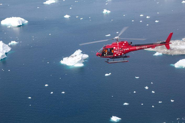 An Air Greenland AS 350 helicopter over icebergs in the Disko Bay near Ilulissat in North Greenland