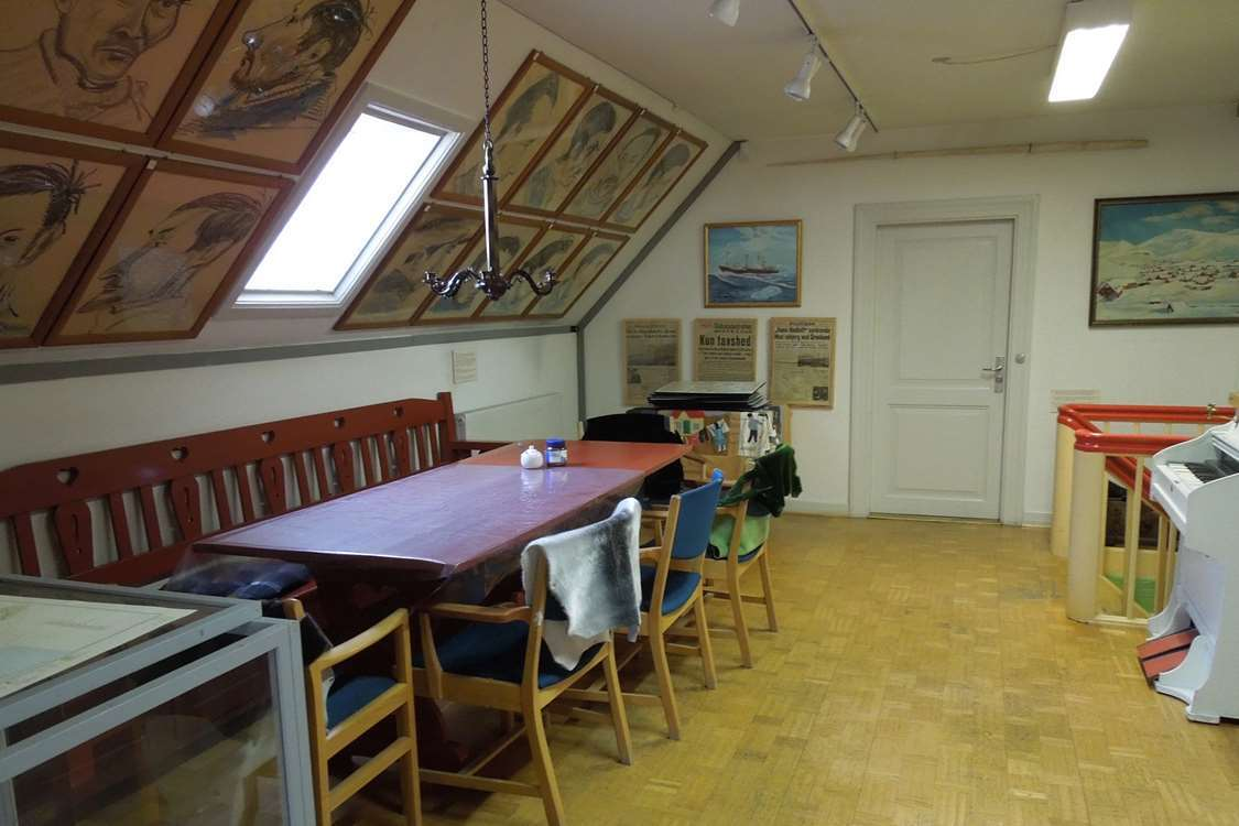 Inside view of Qaqortoq Museum with drawings on the wall, newspaper clips, paintings, sealskin and a piano. Photo by Qaqortoq Museum