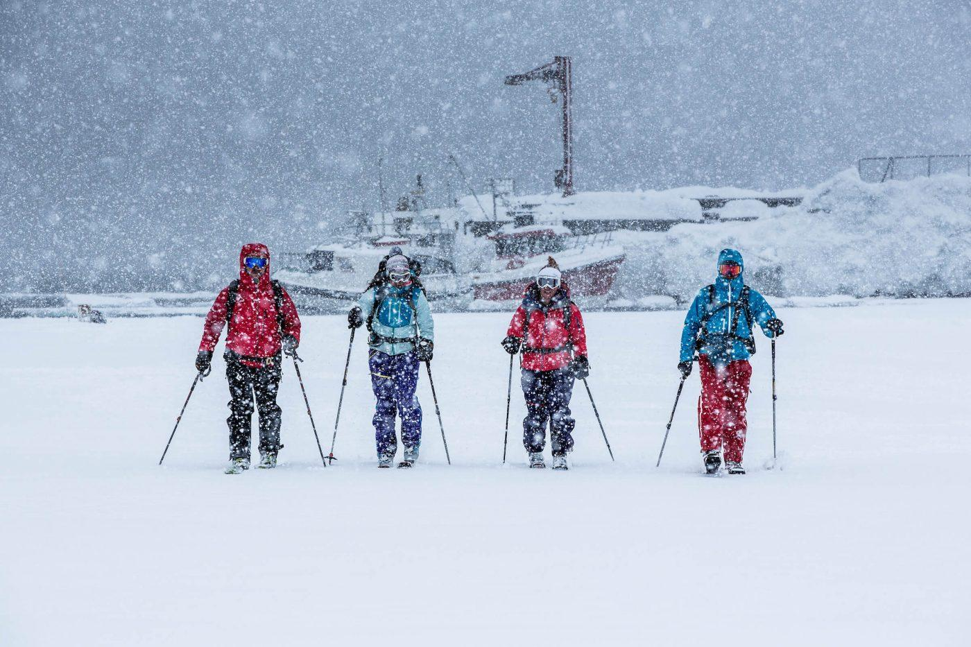 Ski touring skiers in heavy snowfall in Kuummiut in East Greenland. Photo by Mads Pihl