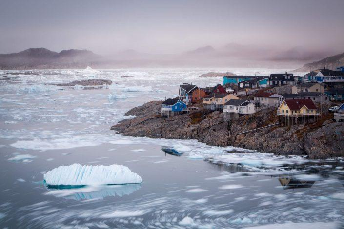 Small icebergs from the Ilulissat Icefjord floating along the coastline of colourful houses in Ilulissat in North Greenland. By Paul Zizka