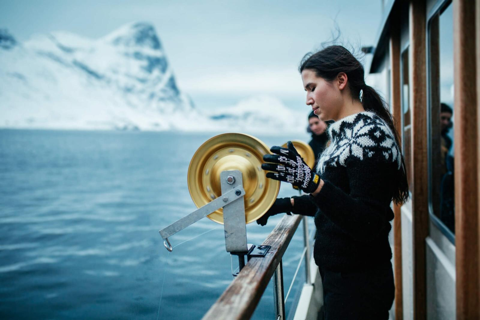 The deckhand Line fishing on a tour with Arctic Boat Charter in the Nuuk fjord in Greenland. Photo by Rebecca Gustafsson