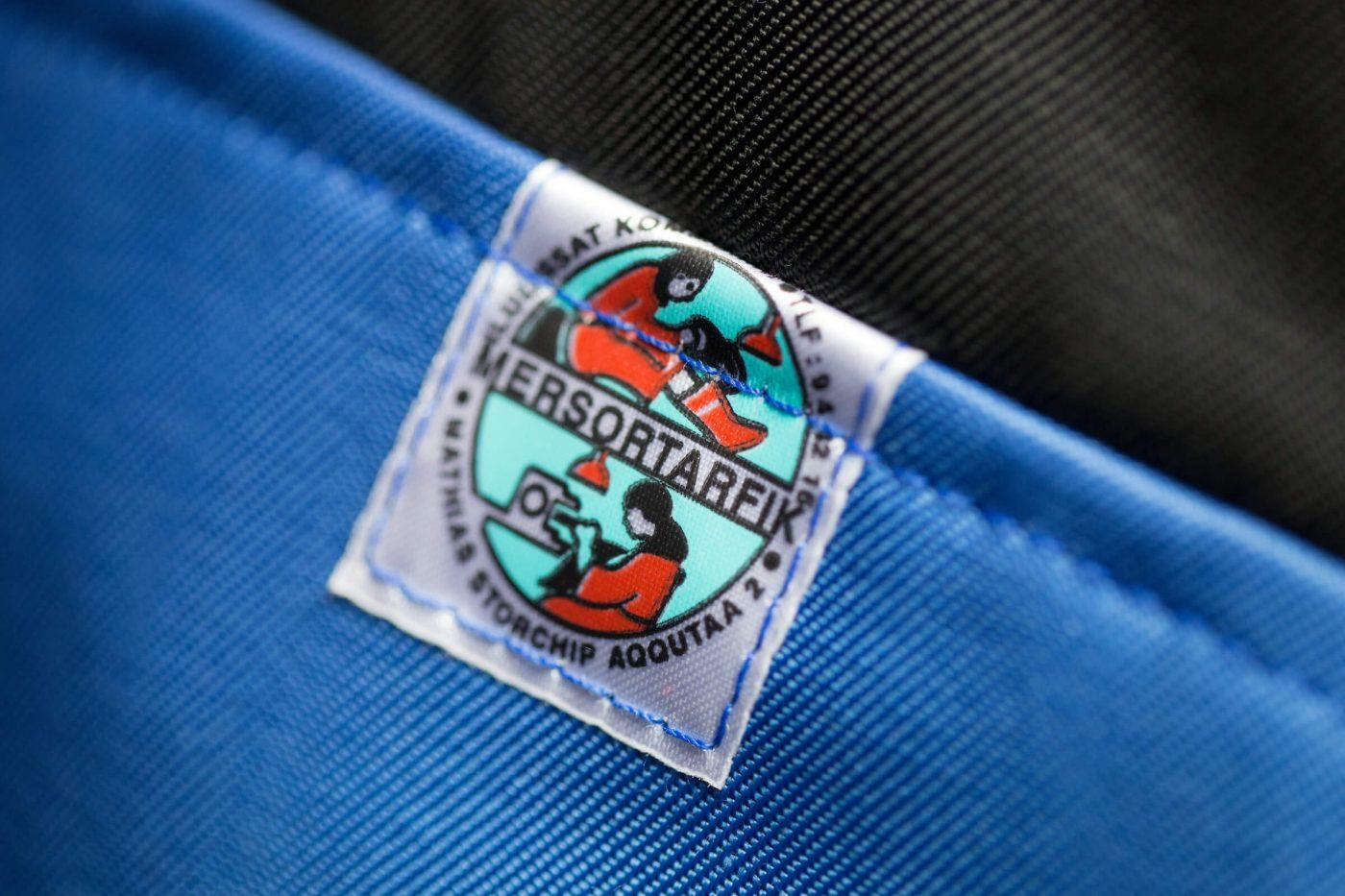 The Mersortarfik sewing workshop logo on one of their blue anoraks in Ilulissat, Greenland. Photo by Mads Pihl