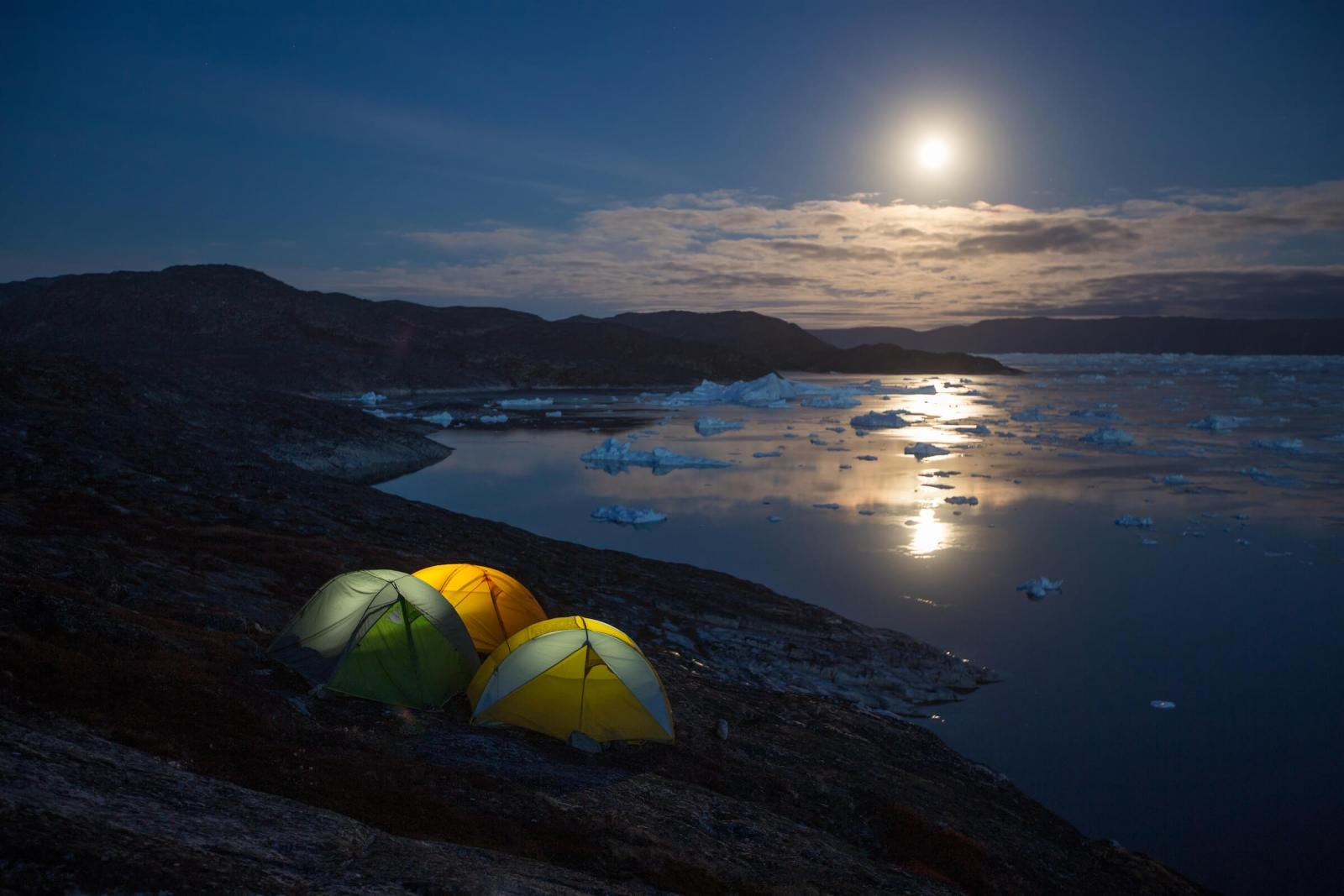 Three tents standing together overlooking the Ilulissat Icefjord in North Greenland under a moonlight sky. By Paul Zizka